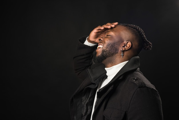 Black man in profile laughing with his hand on his face. close up. black background.