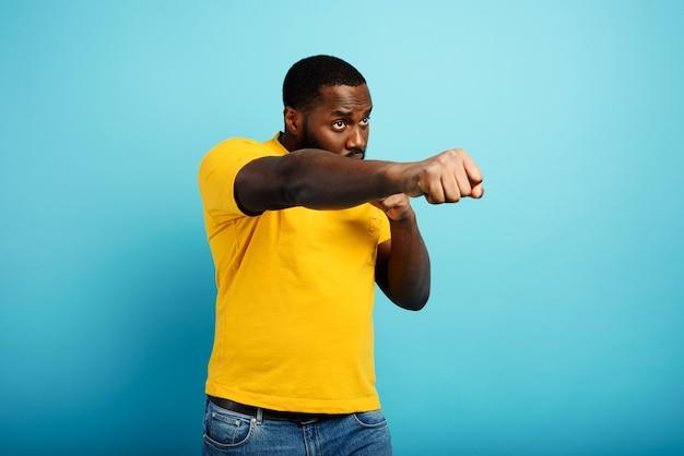 흑인 남자가 펀치를 날리고 무언가에 맞서 싸웁니다. 청록색 배경