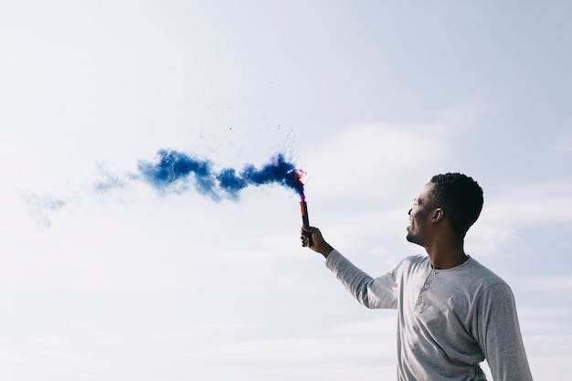Black man raising colored smoke bombs