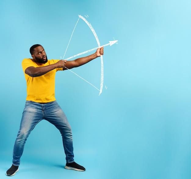 黒人男性は弓から矢を放つ準備ができています。シアンの背景
