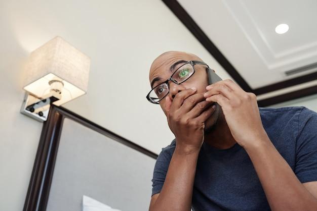 Черный мужчина получает шокирующие новости по телефону и прикрывает рот рукой от волнения