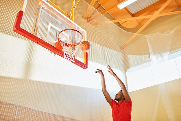 Black man shooting ball into basket