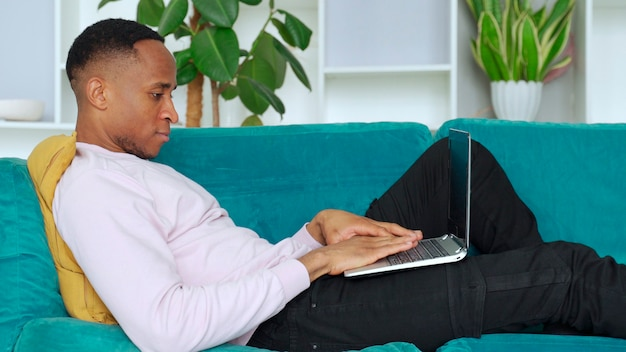 Black man sits on sofa in living room and using laptop for net searching web surfing or texting messages