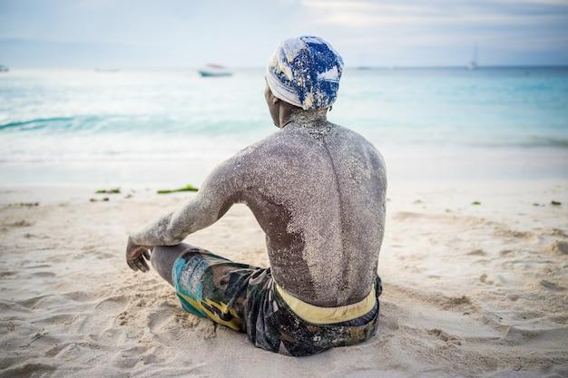 Black man sitting on beach