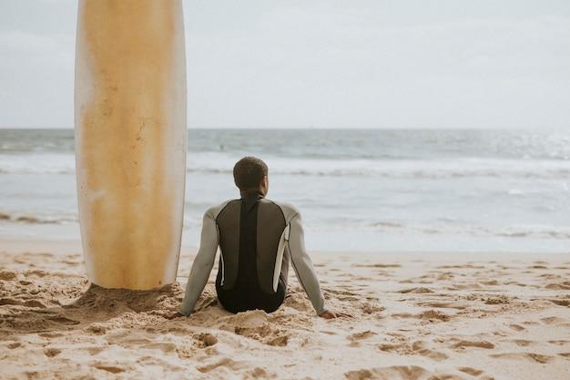 彼のサーフボードのそばに座っている黒人男性