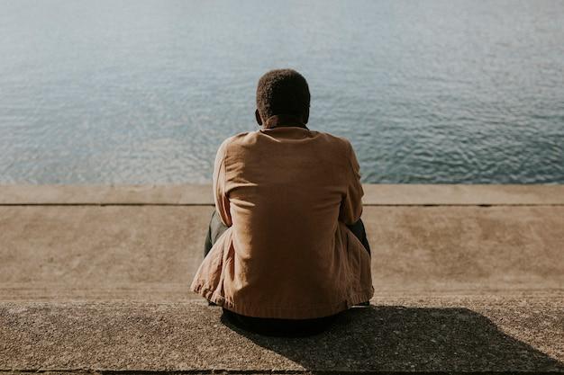 Uomo nero seduto vicino all'acqua