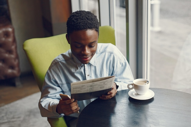 Black man sitting in a cafe and drinking a coffee