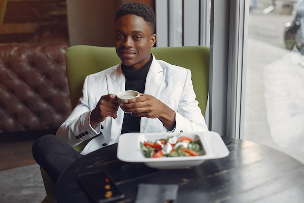 Black man sitting in a cafe and eating a vegetable salad