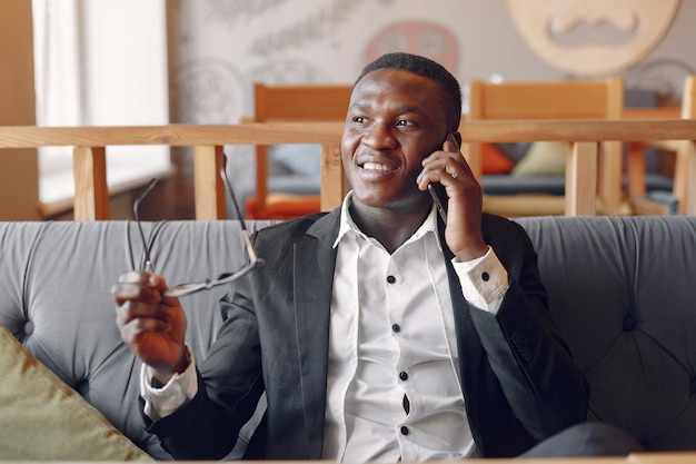Black man sitting in a cafe with phone