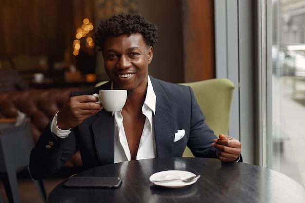 Черный человек сидит в кафе и пьет кофе