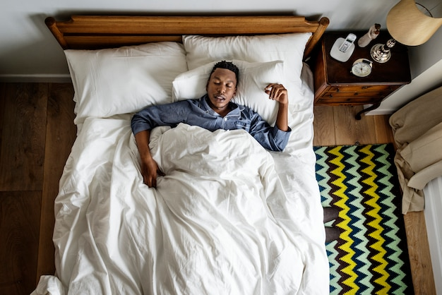 Black man sleeping on bed