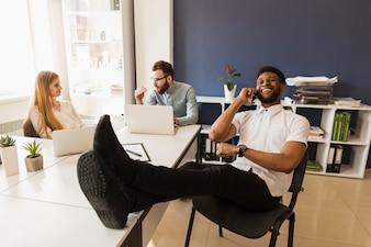Black man speaking on phone in office