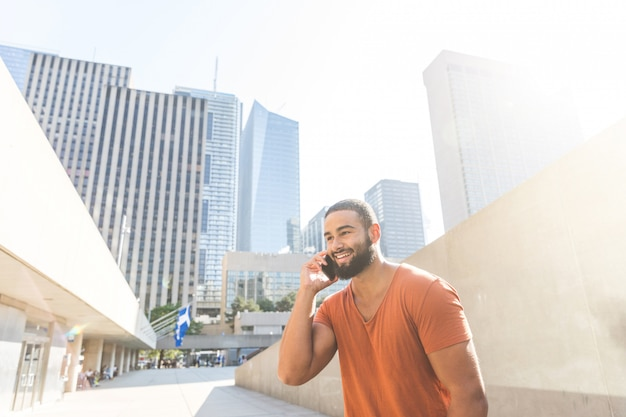 Black man speaking on the phone in the city