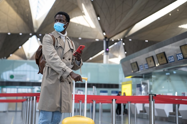 바이러스 전염병, covid-19 동안 얼굴 보호 마스크를 쓰고 공항에 서있는 흑인