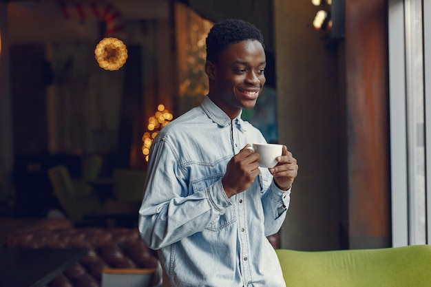 Black man standing in a cafe and drinking a coffee