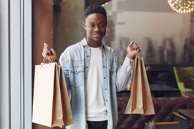 Black man standing in a cafe with shopping bags
