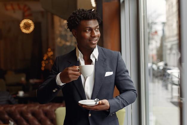 Черный человек стоит в кафе и пьет кофе