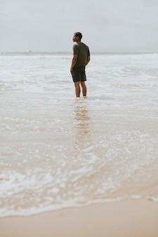 Черный человек, стоящий на пляже