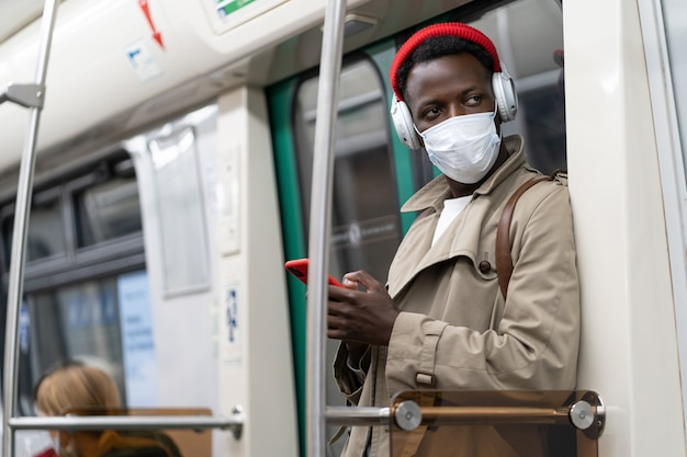 Black man in subway train, wear face mask to protect from virus