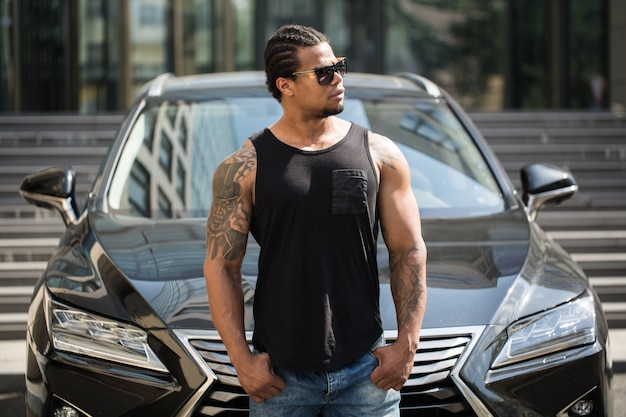 Black man in sunglasses standing near the car with modern building