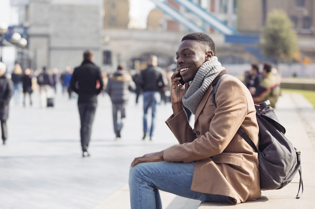 Черный человек разговаривает по мобильному телефону в лондоне