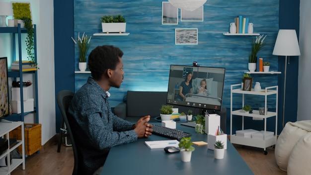 Чернокожий мужчина через веб-камеру разговаривает с женой о здоровье ребенка, пока тот лежит в больничной палате. консультации по медицинской телемедицине и рекомендации по лечению. вызов карантина