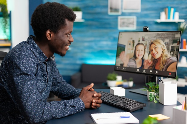 Черный мужчина разговаривает с друзьями и семьей по видеозвонку