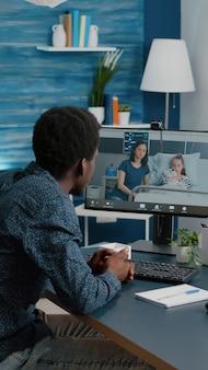 Черный мужчина разговаривает со своей семьей, которая находится в больничной палате