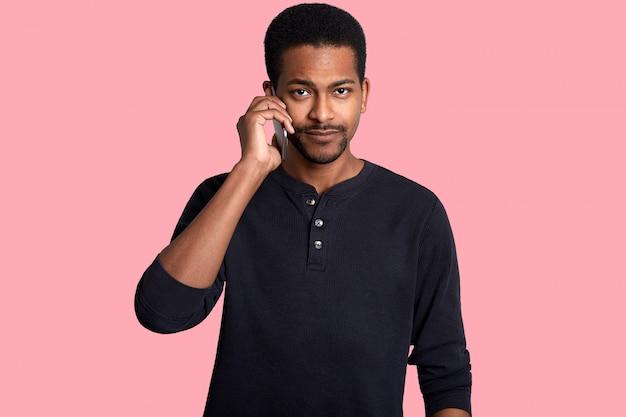 黒人男性が携帯電話で話し、重要なトピックを話し合います。ローズに分離された彼のスマートフォンで悲しそうな表情を持つハンサムなアフリカ人。