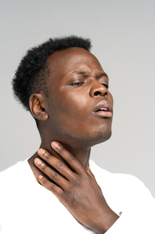 Black man touches fingers of sore throat, thyroid gland isolated on gray background.
