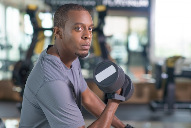 Black man training with dumbbell and looking at camera