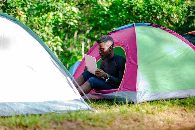 Black man using laptop  outside the camping tent