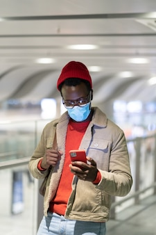 공항 터미널에서 스마트 폰을 사용하는 흑인 남자, 핸드폰을 사용하여 얼굴 의료 마스크를 착용하십시오. 코로나 바이러스 감염증 -19 : 코로나 19.