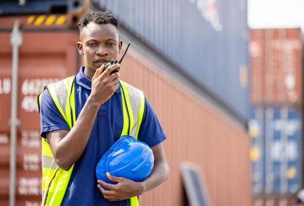 컨테이너 터미널에서 워키토키를 사용하는 흑인, 산업 노동자가 적재를 통제하고 있다