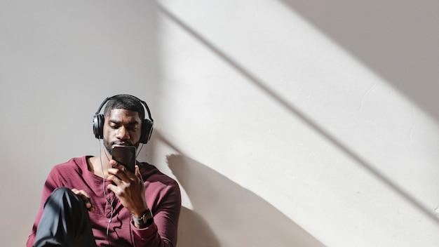 휴대전화로 비디오 클립을 보고 있는 흑인 남성