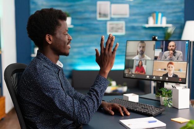 オンラインインターネットとウェブカメラ通信レムを使用してビデオ通話チャットで同僚に手を振っている黒人男性...