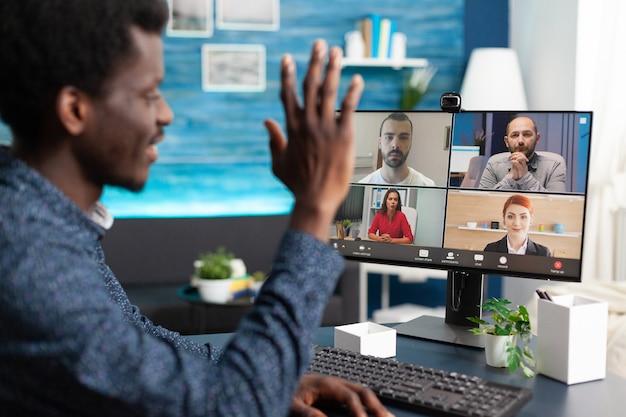ビデオ通話チャットで同僚に手を振っている黒人男性