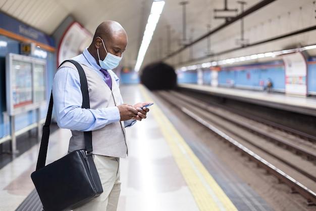地下鉄の駅でスマートフォンを使ってフェイスマスクをかぶった黒人男性。