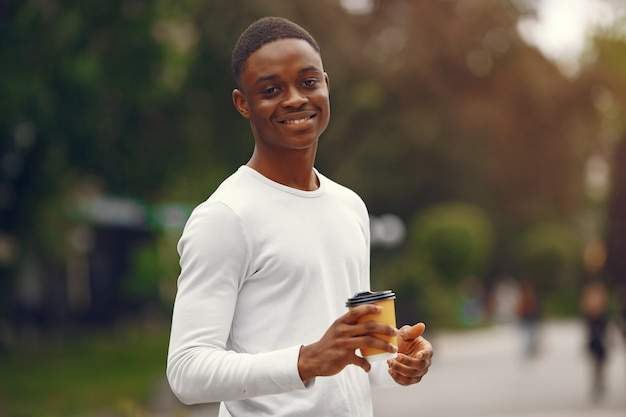 Black man in a white sweater in a summer city