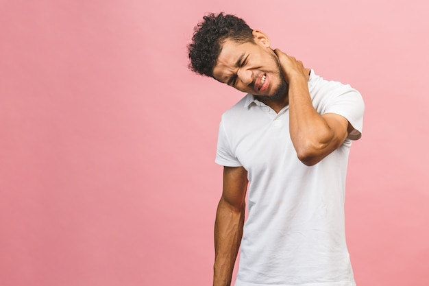 Black man in white t-shirt on pink black background guy feels physical discomfort unhealthy tired closed his eyes for neck pain