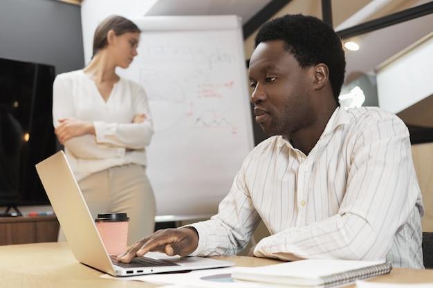 Uomo nero e donna bianca che lavorano insieme in squadra.