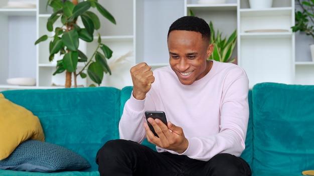 Победитель темнокожего мужчины держит смартфон в эйфории от победы в мобильной онлайн-ставке