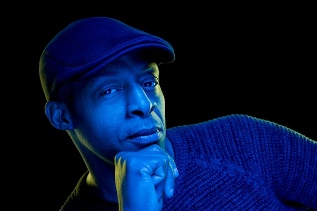 Black man with blue light wearing a flat cap, isolated on black background