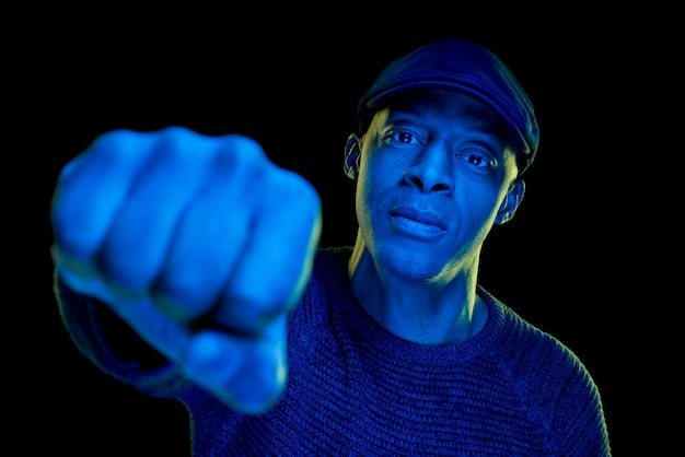 Black man with blue light wearing a flat cap, isolated on black background.