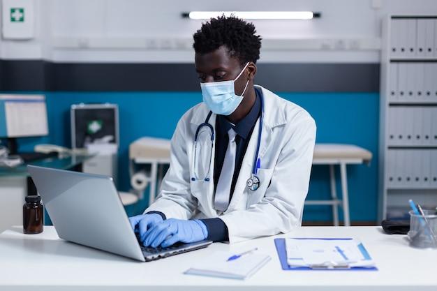 Черный человек с профессией врача, используя ноутбук на столе
