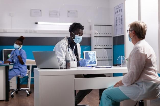 現代のタブレットでx線を保持している医者の職業を持つ黒人男性