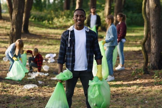 Черный человек с полными пакетами мусора на фоне его друзей, собирающих мусор в лесу.