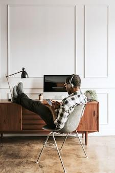 그의 책상에 앉아 그의 전화에 헤드폰을 가진 흑인 남자