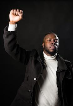Черный человек с поднятым кулаком борется за свои права. средний выстрел. черный фон.