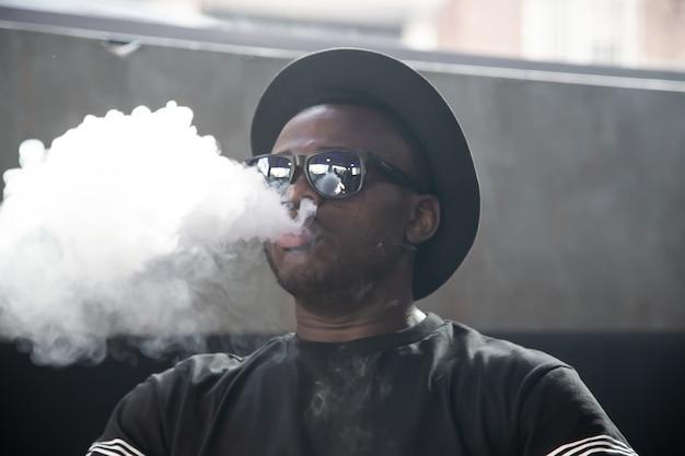 サングラスと帽子の喫煙と煙を吹いている黒人男性